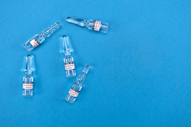 Szklane ampułki z gotową szczepionką covid19 leżą na niebiesko, puste z miejscem na tekst od góry