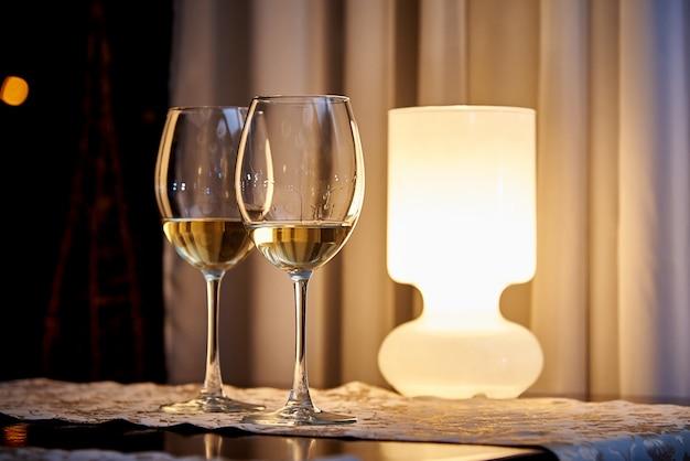 Szklane białe wino na stole z płonącą lampą w przytulnej restauracji.