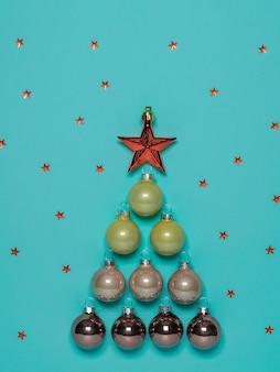 Szklane bombki z gwiazdą ułożone w kształcie choinki.