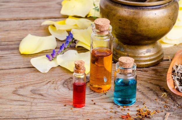 Szklane butelki aromatu olejku na drewnianym, obraz dla medycyny alternatywnej terapii