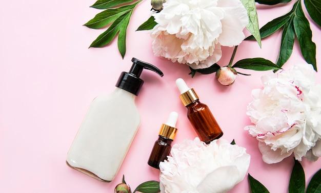 Szklane butelki aromatycznego olejku i kwiaty piwonii na różowym pastelu.