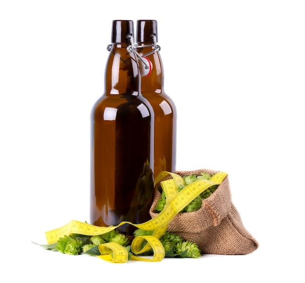 Szklane butelki do piwa kraft ze świeżą zieloną gałązką chmielu i żółtą taśmą pomiarową, na białym tle. pojęcie diety