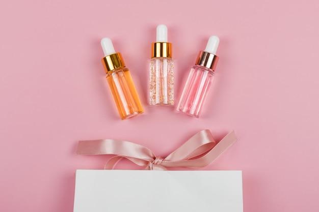 Szklane butelki esencji do pielęgnacji skóry z papierowym prezentem lub torbą na zakupy na różowym tle. witaminy dla skóry