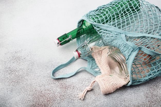 Szklane butelki i słoiki wielokrotnego użytku w siatkowej torbie. zrównoważony styl życia. koncepcja zero zakupów spożywczych