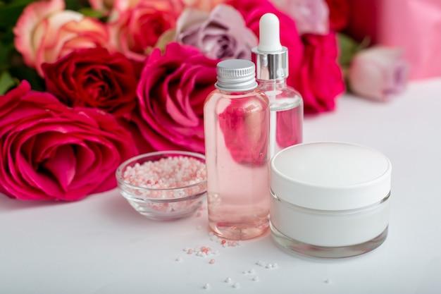 Szklane butelki kosmetyczne, krem, serum, mydło, olej na tle kwiatów biały stół. kwiat czerwony różowy róż naturalny organiczny produkt kosmetyczny. spa, pielęgnacja skóry, kąpiele na ciało. zestaw kosmetyków z różą.
