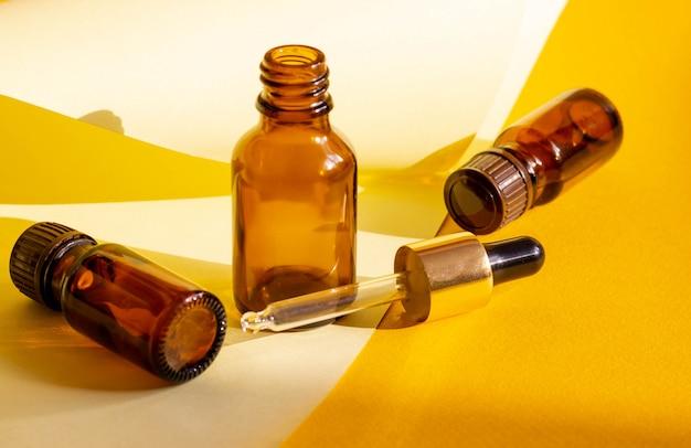 Szklane butelki kosmetyczne na jasnym, piaszczystym żółtym tle z twardymi cieniami. bloger kosmetyczny, koncepcja salon procedur. minimalizm. kosmetyczny wkraplacz na różowym tle.