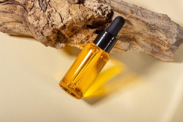 Szklane butelki kosmetyczne z zakraplaczem stoją obok kłody na beżowym tle z jasnym światłem słonecznym. koncepcja kosmetyków naturalnych, naturalny olejek eteryczny