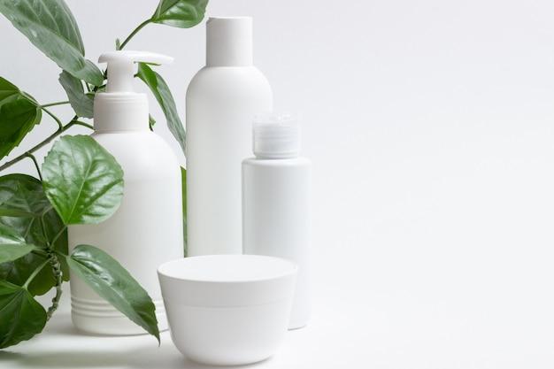 Szklane butelki kosmetyczne z zakraplaczem stoją obok zielonych liści na białym tle. koncepcja kosmetyków organicznych, naturalny olejek i krem.