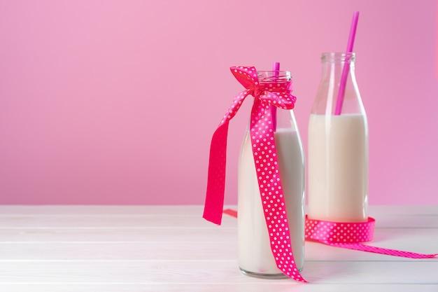 Szklane butelki mleka lub koktajlu mlecznego na różowym tle