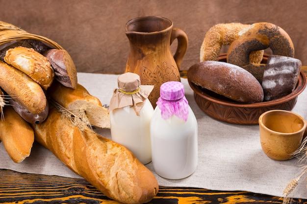 Szklane butelki na mleko przykryte tkaniną, wysoki drewniany dzbanek i kubek obok bochenków francuskiego chleba i bułeczek
