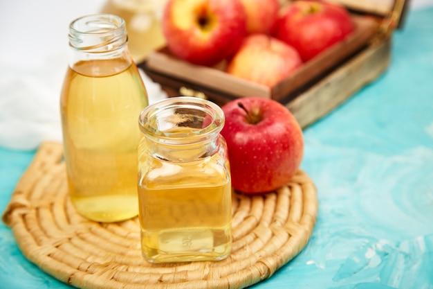 Szklane butelki octu jabłkowego i czerwonych jabłek