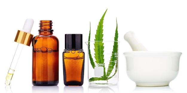 Szklane butelki oleju konopnego i liści konopi na białym tle. koncepcja wykorzystania konopi w medycynie.