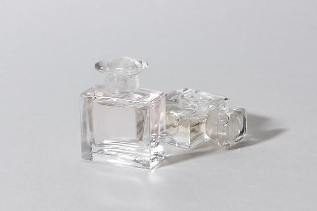 Szklane butelki perfum w jasnym świetle słonecznym z ostrymi cieniami