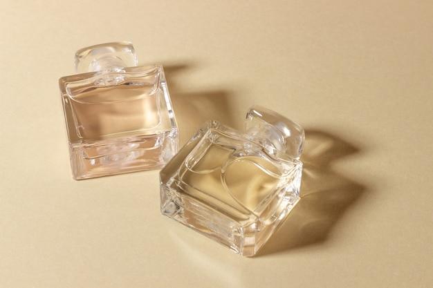 Szklane butelki perfum w jasnym świetle słonecznym z ostrymi cieniami.