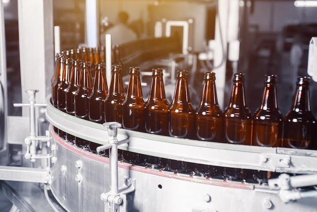 Szklane butelki piwa w kolorze brązowym na linii przenośnika butelkowania piwa