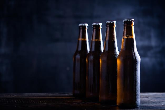 Szklane butelki piwo z szkłem i lodem na ciemnym tle