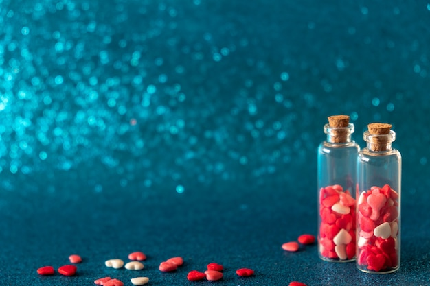 Szklane butelki z cukrem w kształcie serca posypką na błyszczącym niebieskim tle. koncepcja walentynki, słodka miłość.