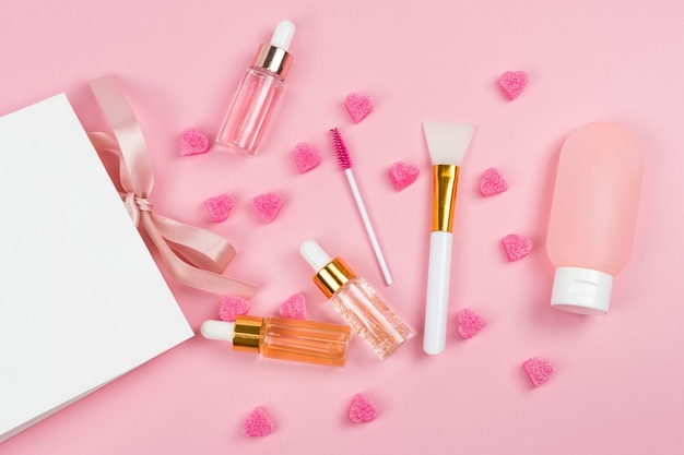 Szklane butelki z esencją do pielęgnacji skóry i balsam do ciała w plastikowym pojemniku z papierową torbą na zakupy na różowym tle