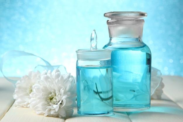 Szklane butelki z esencją koloru na drewnianym stole na niebiesko