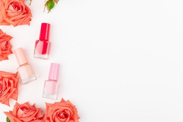 Szklane butelki z kolorowym lakierem do paznokci na białym tle. kolory różowy, czerwony i beżowy.