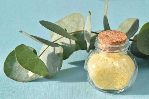 Szklane butelki z solą i gałązką eukaliptusa