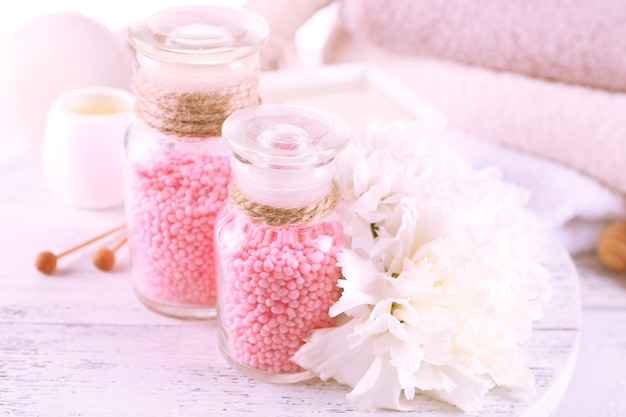 Szklane butelki z solą morską kolor spa na drewnianym stole, zbliżenie