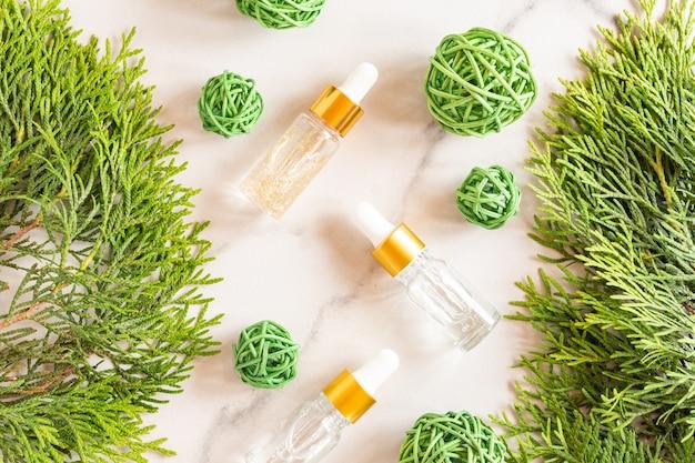 Szklane butelki z zakraplaczem z olejkiem kosmetycznym, olejkiem eterycznym lub serum na marmurowym tle z gałązkami tui i kulkami ratangowymi. pojęcie naturalnych kosmetyków organicznych. ziołowe produkty homeopatyczne.