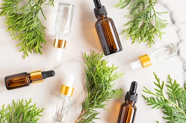 Szklane butelki z zakraplaczem z olejkiem kosmetycznym, olejkiem eterycznym lub serum na marmurowym tle z gałązkami tui. pojęcie naturalnych kosmetyków organicznych. ziołowe produkty homeopatyczne.