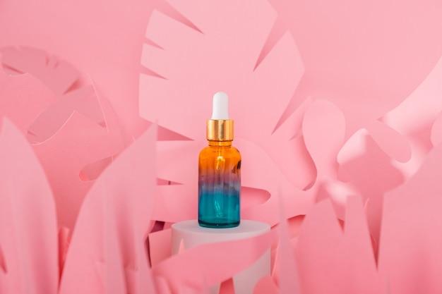 Szklane butelki z zakraplaczem z pipetą stojącą na białym podium. przezroczysty hialuronowy naturalny kosmetyk mineralny i koncepcja pielęgnacji skóry eko serum.
