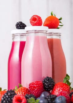 Szklane butelki ze świeżym letnim koktajlem z jagodami na drewnianym stole. truskawki i maliny z jagodami i jeżynami.