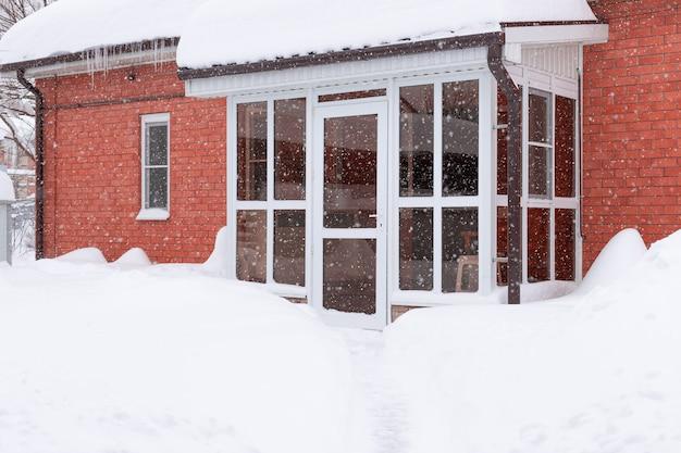 Szklane drzwi wejściowe domu z czerwonej cegły podczas obfitych opadów śniegu mroźna sceneria przyrody w zimie