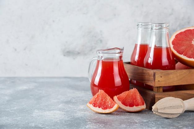 Szklane dzbanki soku grejpfrutowego z kawałkami owoców.