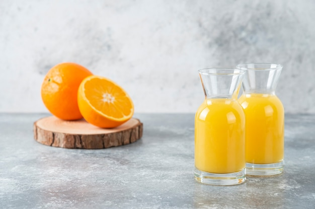 Szklane dzbanki soku z plastrem pomarańczy.