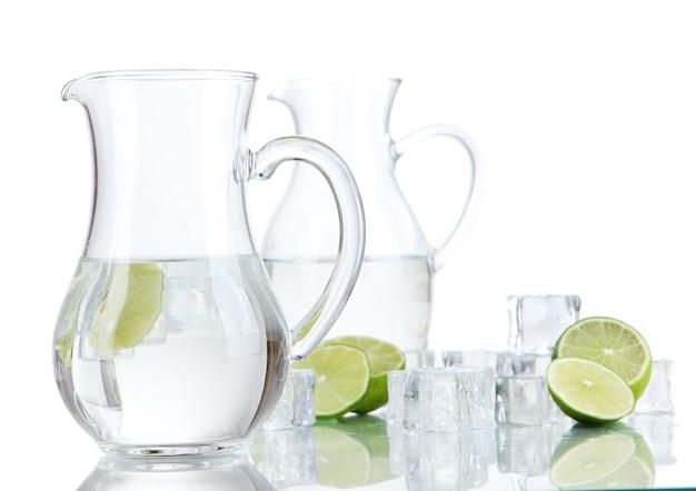 Szklane dzbany wody z lodem i wapnem na białym tle