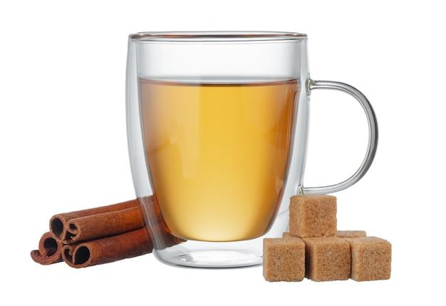 Szklane filiżanki herbaty i cynamonu na białym tle