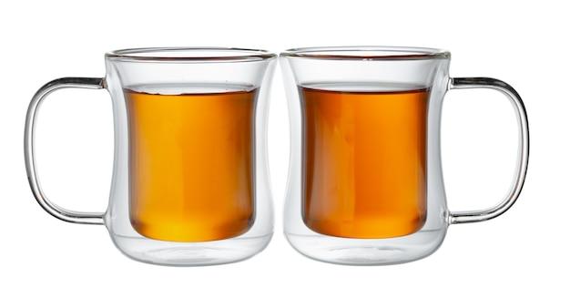 Szklane filiżanki herbaty na białym tle