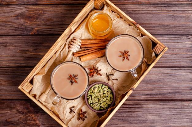 Szklane filiżanki tradycyjnej indyjskiej chai masala herbaty na tacy z składnikami.