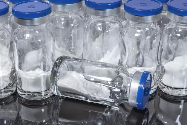 Szklane fiolki z medyczną szczepionką w proszku na ciemnym tle