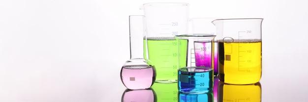 Szklane kolby z wielobarwnym płynem na stole