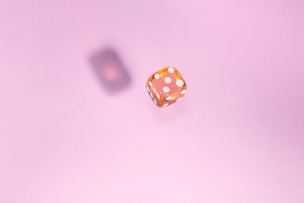 Szklane kości spadają, kość do gry na różowym tle.