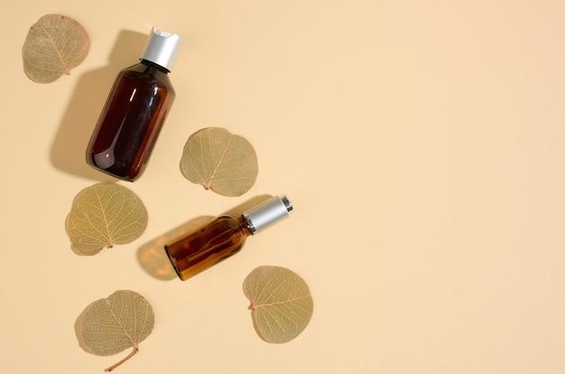 Szklane kosmetyczne brązowe butelki na beżowym tle. makieta marki kosmetyków spa, widok z góry
