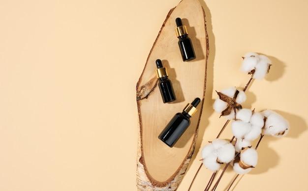 Szklane kosmetyczne brązowe butelki z pipetą na beżowym tle. makieta marki kosmetyków spa, widok z góry