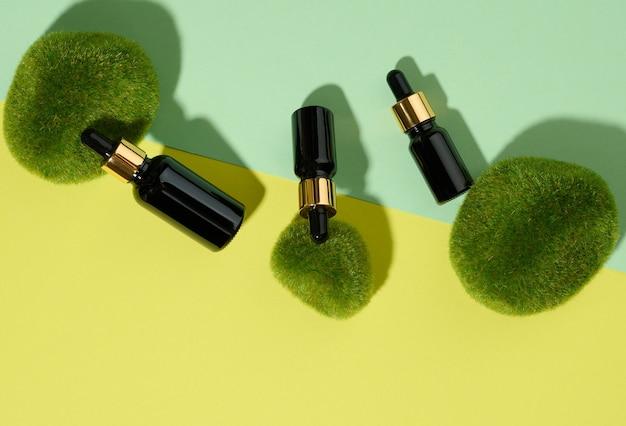 Szklane kosmetyczne brązowe butelki z pipetą na zielono-żółtym tle z kawałkami mchu. makieta marki kosmetyków spa, widok z góry