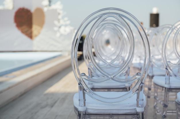 Szklane krzesła stoją w rzędzie podczas pięknej ceremonii ślubnej.
