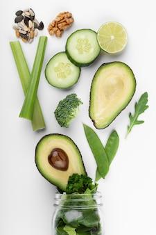 Szklane kubki słoikowe z liśćmi sałaty zielonych warzyw zdrowotnych, limonki, jabłka, kiwi, awokado
