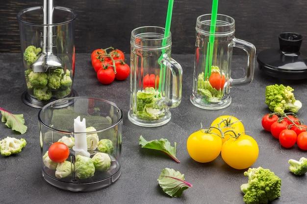 Szklane kubki z brokułami i zielonymi słomkami.