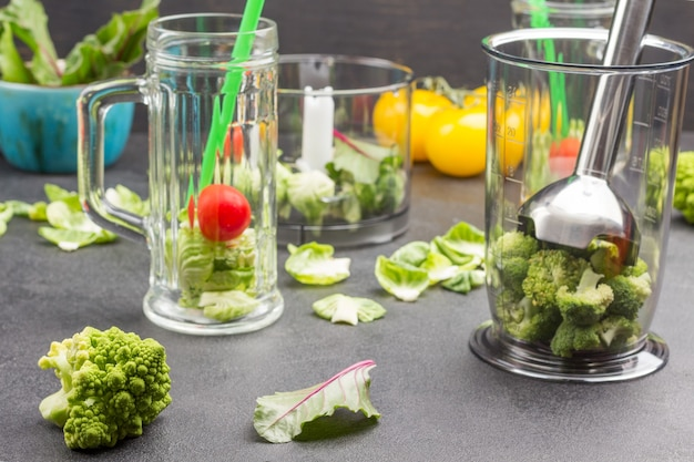 Szklane kubki z brokułami, pomidorami i zielonymi słomkami. miska blendera z metalową niszczarką