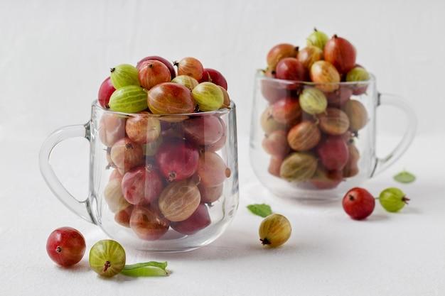 Szklane kubki z organicznym agrestem na białym stole