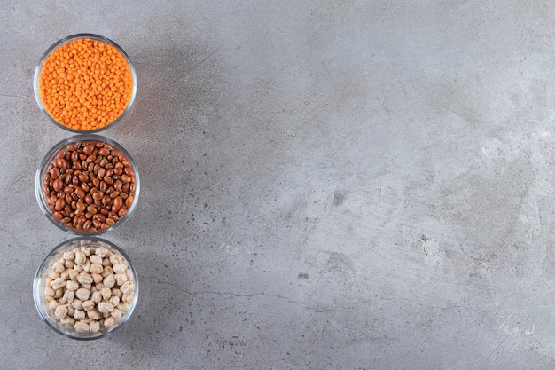 Szklane miski pełne surowej soczewicy, grochu i fasoli na kamiennym tle.