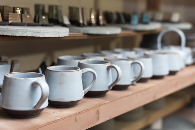 Szklane naczynia ceramiczne stoją na półce w regale warsztatowym z ręcznie wykonanymi kubkami ceramicznymi i glinianymi